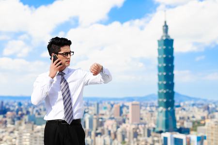 business man speak phone and look smart phone in the taipei