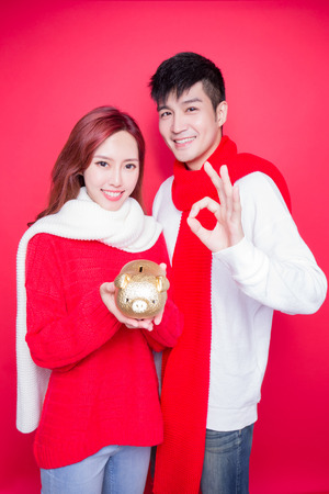 couple take piggy bank with chinese new year on red background