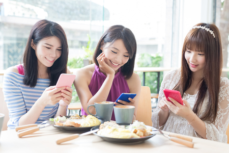 happy woman friends use phone in restaurant