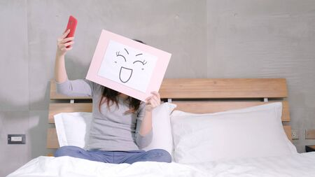 woman take smile board and selfie on the bed