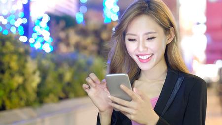 femme d'affaires sourire et utiliser le téléphone le soir
