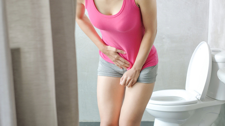 woman with urine urgency in the toilet Stockfoto
