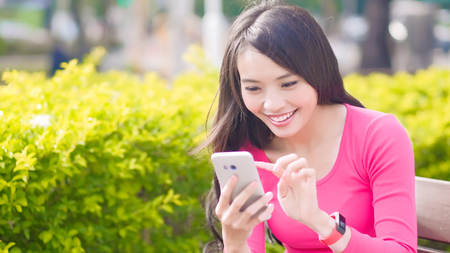 woman use phone and smile happily in the park