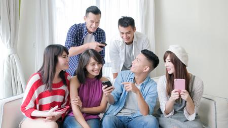 os jovens usam o telefone e sorriem felizmente