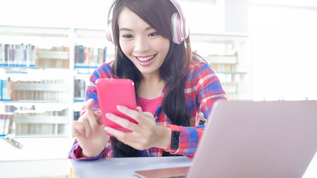 woman student listen music and use cell phone in the library