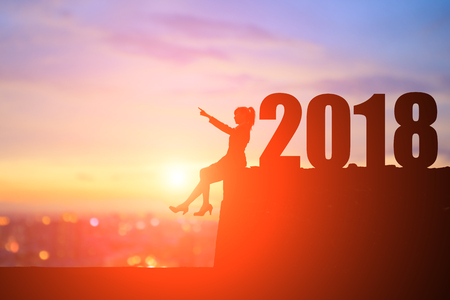 silhouette of businesswoman show something and sit on the cliff with 2018