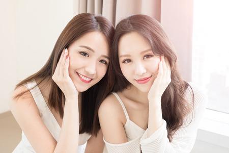 twee schoonheid vrouw glimlach naar je in het huis