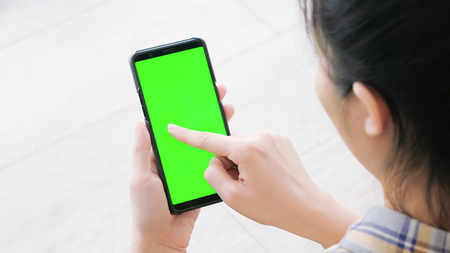 woman take cell phone with green screen in the home 版權商用圖片