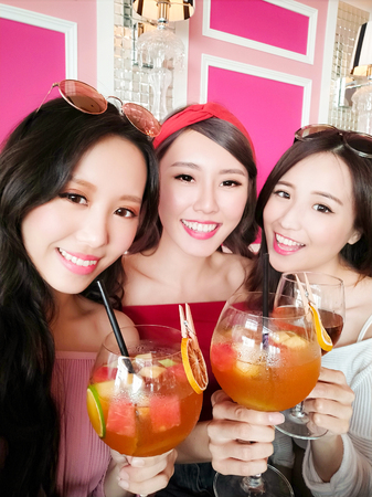 three beauty woman selfie happily and take juice in the restaurant