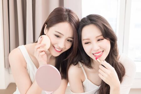 two beauty woman take puff and lipstick in room Stock Photo