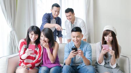 若者は電話を使い、楽しく笑顔を見せる