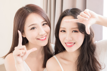 two beauty woman making frame gesture in the home Stock Photo