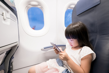 cute girl paly phone in the airplane Фото со стока