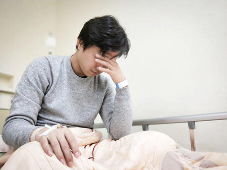 Patient man with headache on the hospital bed