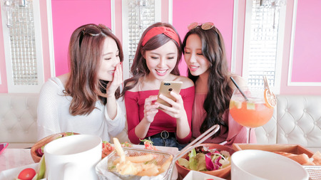 women feel bad and use phone in restaurant Stock Photo