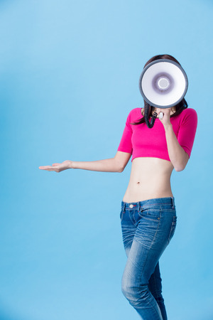 woman take microphone with slim waist on the blue background Stock Photo