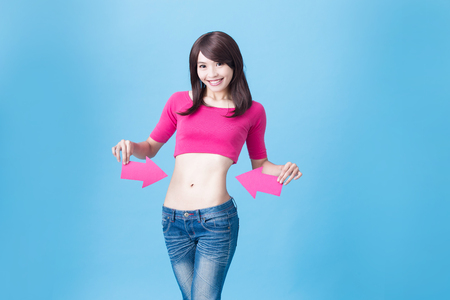 Woman take arrow and show her waist on the blue background