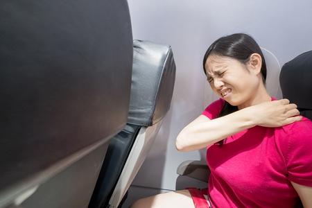 vrouw van middelbare leeftijd voelt pijn in de schouder in het vliegtuig Stockfoto