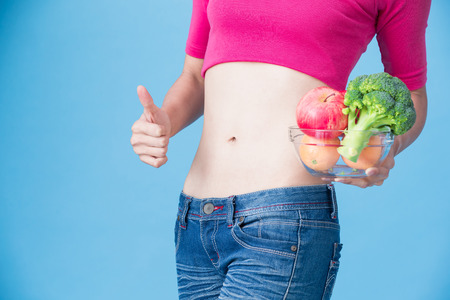 woman take vegetable with body health concept on the blue background