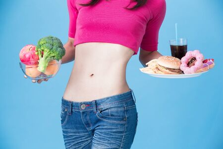 woman choose vegetable or junk food with body health concept on the blue background