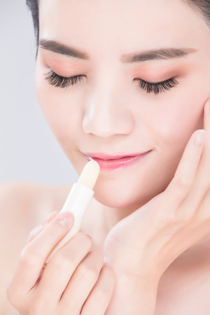 woman use lip balm on the gray background Standard-Bild