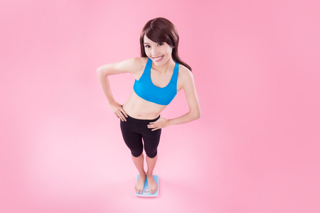 woman stand on weight scale with pink background