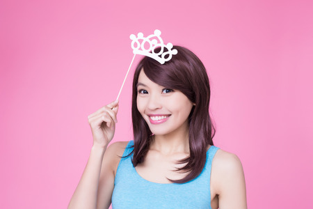 woman holding paper party sticks on the pink background