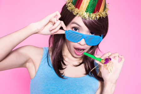 young woman with party hat and noisemaker on the pink background Standard-Bild