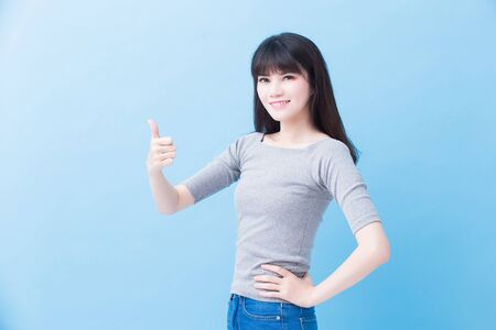 young woman student thumb up on the blue background Standard-Bild