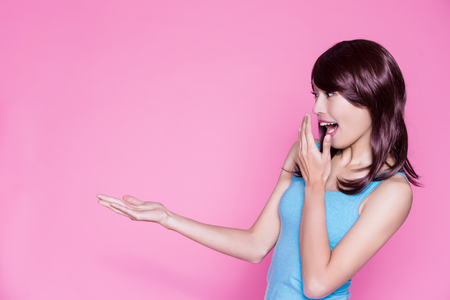 woman feel surprise and show something to you on the pink background