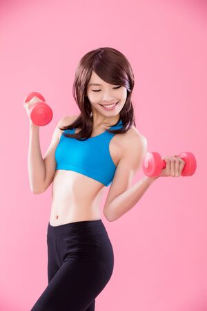 beauty sport woman take dumbbell on the pink background