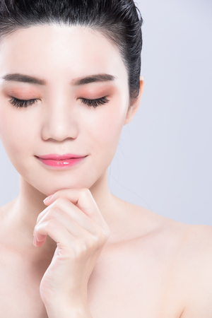 woman close eyes and touch chin with beauty skin care concept on the gray background