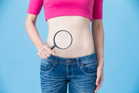 woman take magnifying with belly on the blue background