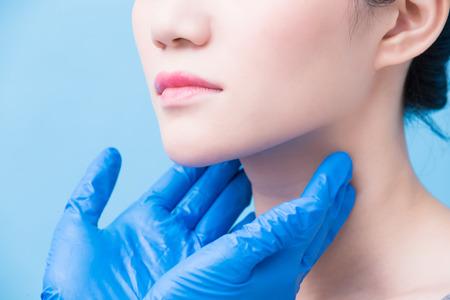 Las mujeres con problemas de la glándula tiroides en el fondo azul.