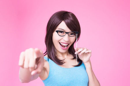 woman holding paper party sticks and pointing to you on the pink background