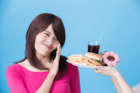 kobieta z koncepcją niezdrowe ciało na niebieskim tle