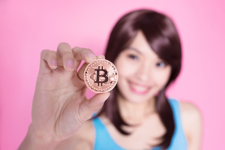 woman take bitcoin on the pink background
