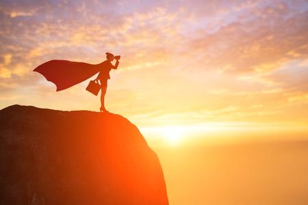 silhouette of super business woman take binocular on mountain