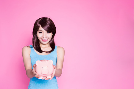 woman take piggy bank on the pink background
