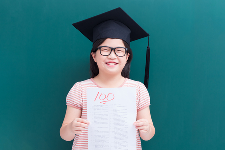 cute girl get test with full score on blank green chalkboard Foto de archivo