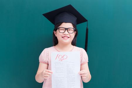 cute girl get test with full score on blank green chalkboard Standard-Bild