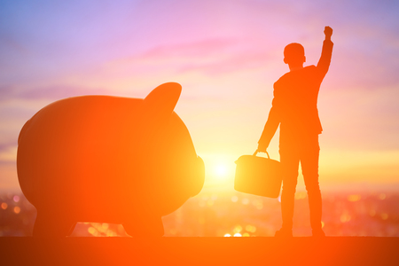 silhouette of business man feel exctied with piggy bank