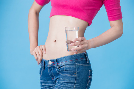 woman take water with belly health concept on the blue background