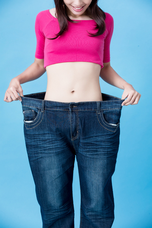 woman wear jeans and show weight loss with slim waist on the blue background