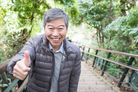 old man smile happily and thumb up in the park 免版税图像