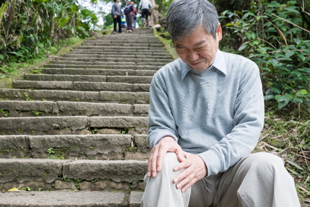 old man with knee problem in the moutain Stock Photo