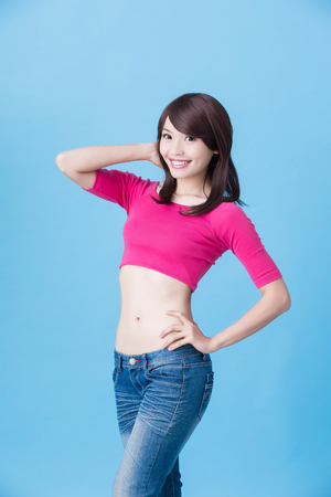 woman smile happily to you with slim waist on the blue background Stock Photo