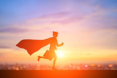 silhouette of super business woman run with sunset Foto de archivo