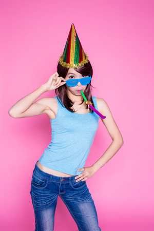 young woman with party hat and noisemaker on the pink background Stock Photo
