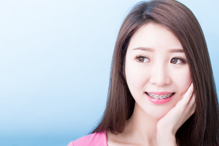 woman wear brace look somewhere and smile happily on the blue background